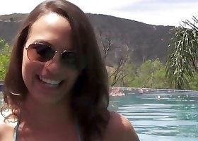Shades-wearing brunette swimming in a pool, giving a titjob