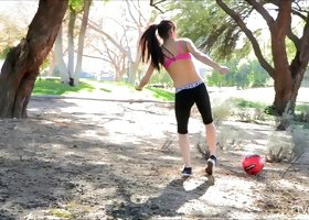 A sporty sexbomb plays some topless soccer in the public park