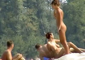 Naked hot bodies bathing in the sun at the nudist beach