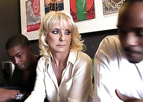 Mature blonde white woman in the company of black men